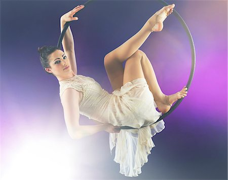 flexible (people or objects with physical bendability) - Aerialist poised on hoop against purple background Stock Photo - Premium Royalty-Free, Code: 614-06897005