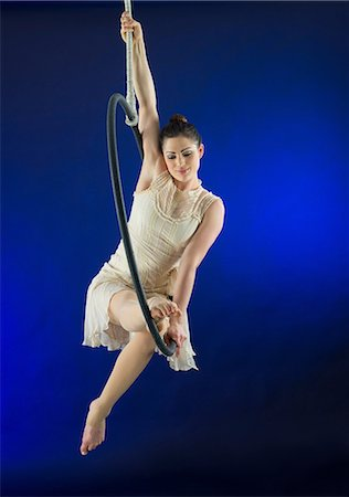 flexible (people or objects with physical bendability) - Aerialist poised on hoop against blue background Stock Photo - Premium Royalty-Free, Code: 614-06897006