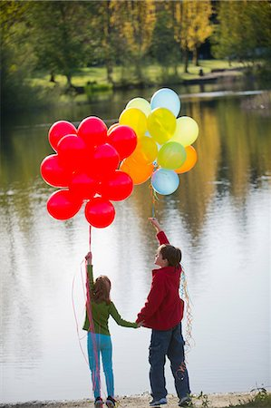 Brother and sister with bunches of balloons in park Stock Photo - Premium Royalty-Free, Code: 614-06897019