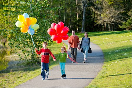 Family walking through park with bunches of balloons Stock Photo - Premium Royalty-Free, Code: 614-06897025