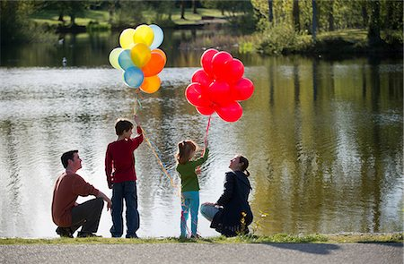 Family in front of lake with bunches of balloons Stock Photo - Premium Royalty-Free, Code: 614-06897022