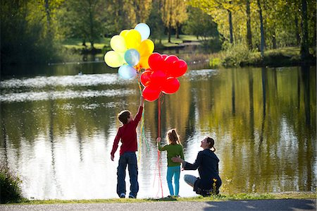 fun - Mother and children in front of lake with bunches of balloons Stock Photo - Premium Royalty-Free, Code: 614-06897023