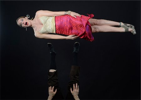 Studio shot of female acrobat mid air, lying on side Stock Photo - Premium Royalty-Free, Code: 614-06897047