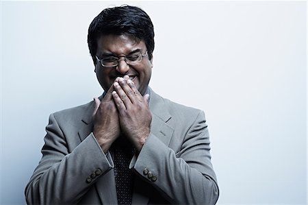 Studio portrait of mid adult male with hands over mouth laughing Stock Photo - Premium Royalty-Free, Code: 614-06897198