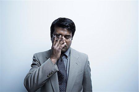 east indian (male) - Studio portrait of businessman rubbing his eye Stock Photo - Premium Royalty-Free, Code: 614-06897200