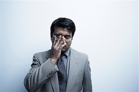 east indian (male) - Studio portrait of businessman rubbing his eye Stock Photo - Premium Royalty-Free, Code: 614-06897200