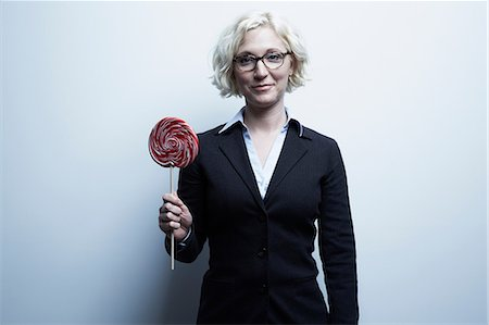 picture of a red lollipop - Studio portrait of blond businesswoman with red lollipop Stock Photo - Premium Royalty-Free, Code: 614-06897245