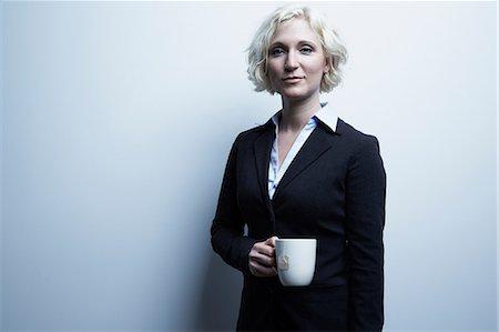 Studio portrait of blond businesswoman holding mug of tea Stock Photo - Premium Royalty-Free, Code: 614-06897248