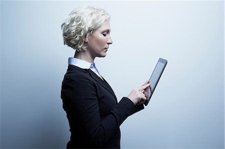 Studio portrait of blond businesswoman looking at digital tablet Stock Photo - Premium Royalty-Free, Code: 614-06897242