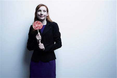 picture of a red lollipop - Studio portrait of young businesswoman holding red lollipop Stock Photo - Premium Royalty-Free, Code: 614-06897253