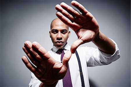 extremism - Studio portrait of businessman with exaggerated hands Stock Photo - Premium Royalty-Free, Code: 614-06897261