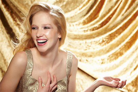 Candid portrait of young woman in front of gold curtain Stock Photo - Premium Royalty-Free, Code: 614-06897300