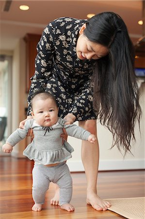 Mother helping baby girl to walk Stock Photo - Premium Royalty-Free, Code: 614-06897325