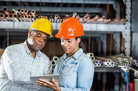 Man and woman in warehouse looking at digital tablet Stock Photo - Premium Royalty-Free, Code: 614-06897370