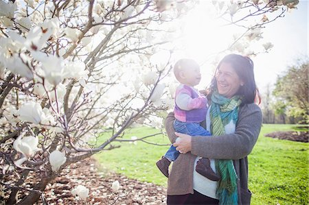 Portrait of baby girl and grandmother next to magnolia blossom Stock Photo - Premium Royalty-Free, Code: 614-06897399