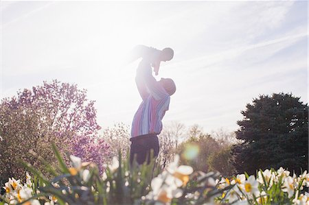 spring - Grandfather holding up granddaughter in garden Stock Photo - Premium Royalty-Free, Code: 614-06897390