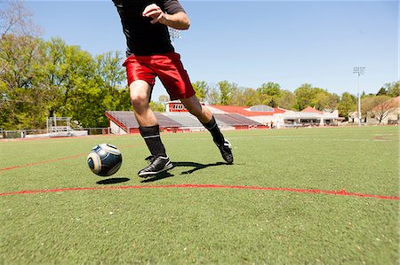 soccer player (male) - Soccer player running down pitch with ball Stock Photo - Premium Royalty-Free, Code: 614-06897426