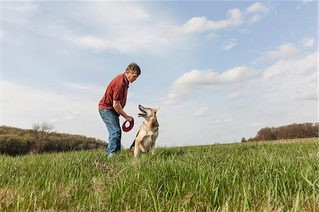 dogs in nature - Man training alsatian dog with red frisbee Stock Photo - Premium Royalty-Free, Code: 614-06897422