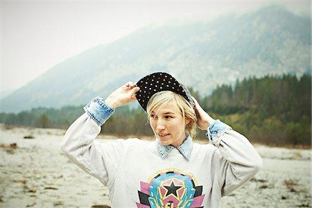 Woman putting cap headwear on Stock Photo - Premium Royalty-Free, Code: 614-06897502