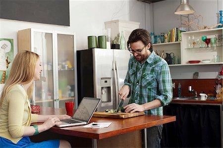 Woman on laptop computer, man chopping vegetables Stock Photo - Premium Royalty-Free, Code: 614-06897561