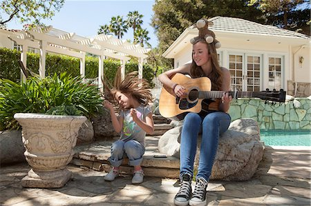Girl with older sister playing guitar Stock Photo - Premium Royalty-Free, Code: 614-06897645