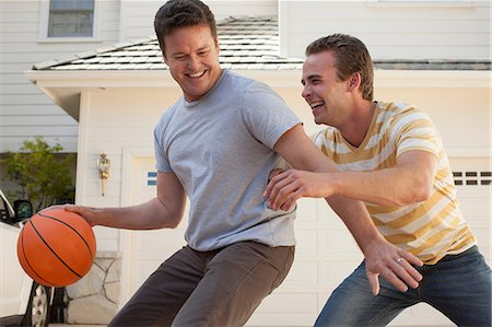 Father and adult son playing basketball Stock Photo - Premium Royalty-Free, Code: 614-06897678