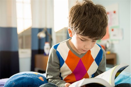 Boy sitting on bed reading book Stock Photo - Premium Royalty-Free, Code: 614-06897714