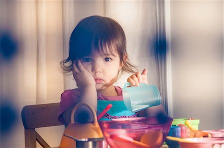 sad girls - Sad girl playing with toys Stock Photo - Premium Royalty-Free, Code: 614-06897710