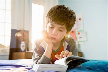 Boy lying on bed reading book Stock Photo - Premium Royalty-Free, Code: 614-06897712
