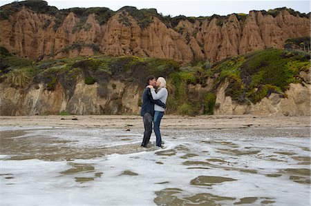 Mature couple standing in sea kissing Stock Photo - Premium Royalty-Free, Code: 614-06897721