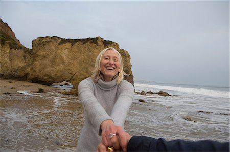 Mature couple holding hands on beach Stock Photo - Premium Royalty-Free, Code: 614-06897723