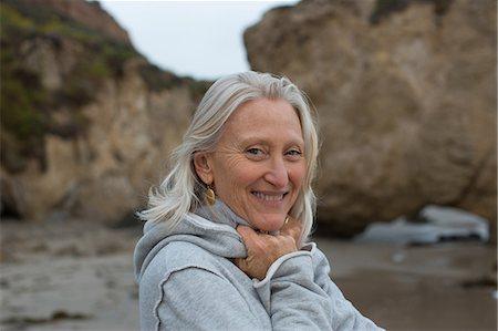 Mature woman wearing grey sweater on beach, smiling Stock Photo - Premium Royalty-Free, Code: 614-06897740