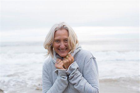 Mature woman wearing grey sweater on beach, smiling Stock Photo - Premium Royalty-Free, Code: 614-06897741