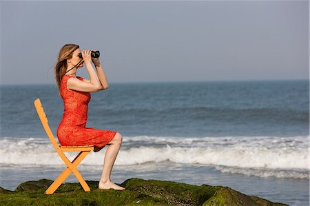 Mature woman sitting on chair on beach with binoculars Stock Photo - Premium Royalty-Free, Code: 614-06897787