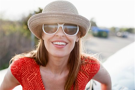 dark glasses - Mature woman wearing sunglasses and sunhat smiling towards camera Stock Photo - Premium Royalty-Free, Code: 614-06897794