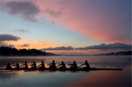 sport rowing teamwork - Nine people rowing at sunset Stock Photo - Premium Royalty-Free, Code: 614-06897795