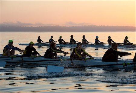 sport rowing teamwork - Fourteen people rowing at sunset Stock Photo - Premium Royalty-Free, Code: 614-06897797
