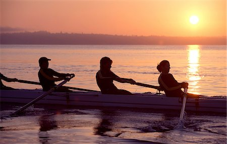 sport rowing teamwork - Four people rowing at sunset Stock Photo - Premium Royalty-Free, Code: 614-06897800