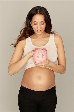 portrait of pregnant woman - Pregnant woman holding piggy bank Stock Photo - Premium Royalty-Free, Code: 614-06897861
