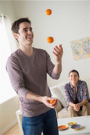 smiling - Man juggling oranges, woman watching Stock Photo - Premium Royalty-Free, Code: 614-06897909