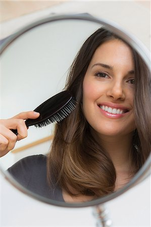 Young woman brushing hair in mirror Stock Photo - Premium Royalty-Free, Code: 614-06897917