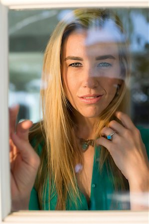 Portrait of young woman looking through window, hand in hair Stock Photo - Premium Royalty-Free, Code: 614-06897927
