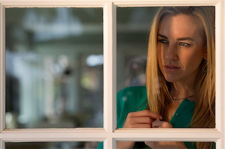 Portrait of young woman looking through window Stock Photo - Premium Royalty-Free, Code: 614-06897928