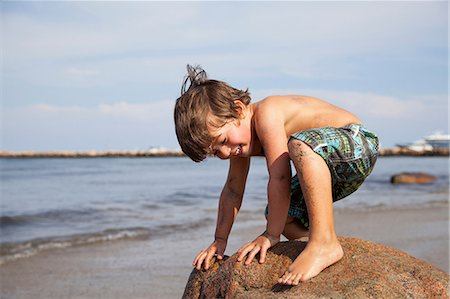 Boy crouching on rock on beach Stock Photo - Premium Royalty-Free, Code: 614-06898004