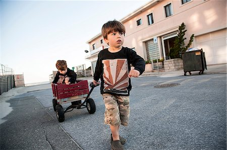pulling - Boy pulling brother along in cart Stock Photo - Premium Royalty-Free, Code: 614-06898002