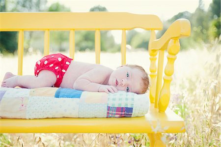 Newborn baby girl lying on yellow bench in field Stock Photo - Premium Royalty-Free, Code: 614-06898011