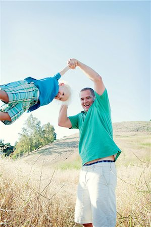 father with two sons not girls - Man swinging son in field Stock Photo - Premium Royalty-Free, Code: 614-06898024