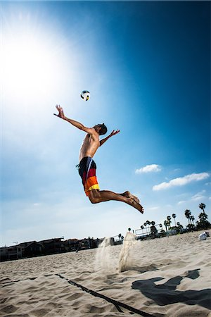 sports - Male beach volleyball player jumping mid air to hit ball Stock Photo - Premium Royalty-Free, Code: 614-06898032