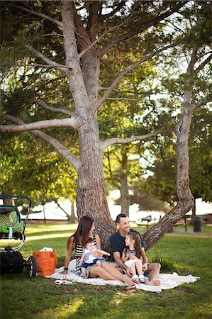 sitting under tree - Family with two children sitting on picnic blanket under tree Stock Photo - Premium Royalty-Free, Code: 614-06898058