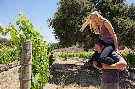 Young couple in vineyard, man giving woman piggy back Stock Photo - Premium Royalty-Free, Code: 614-06898135